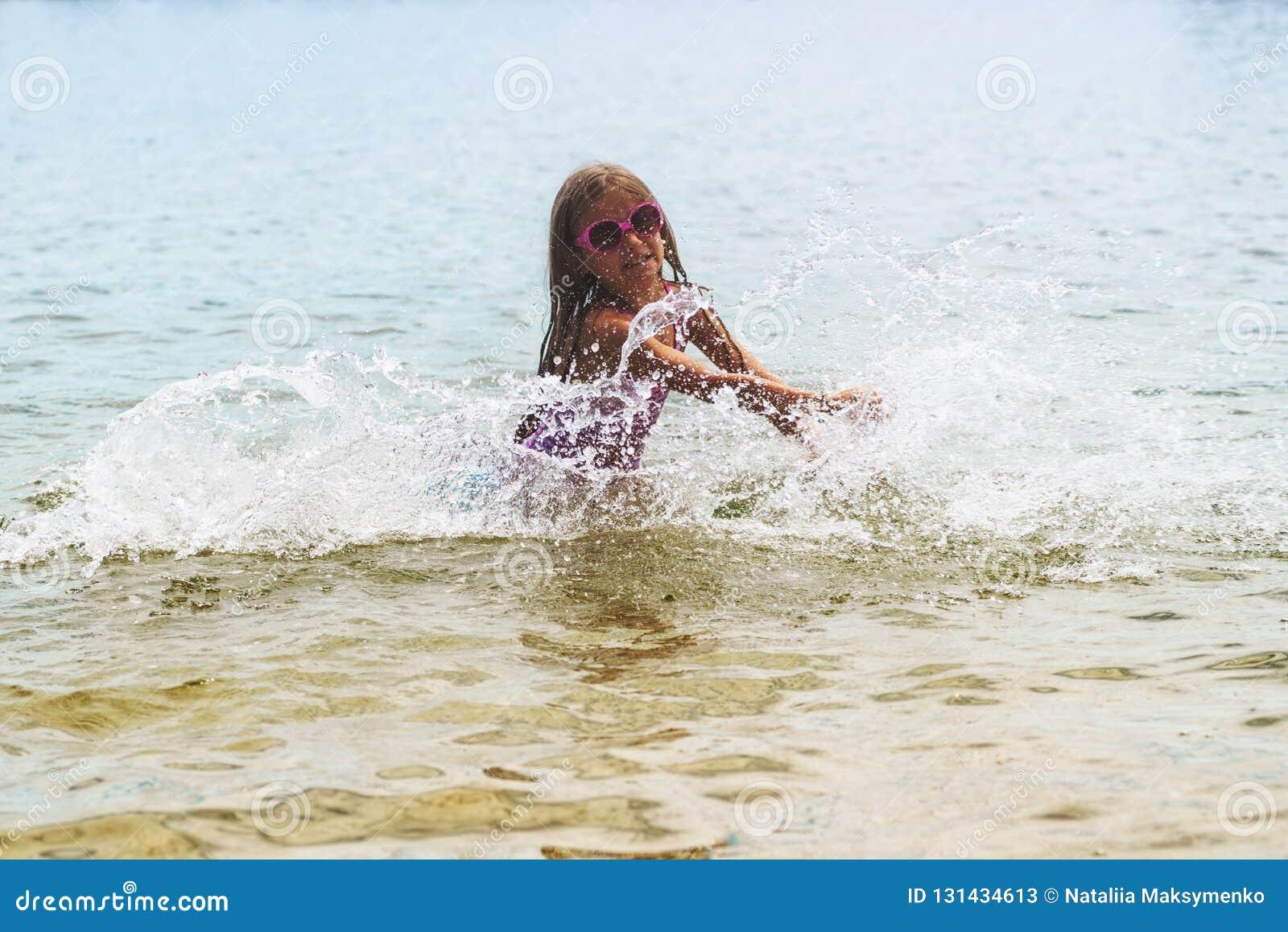 Szczęśliwa mała dziewczynka bawić się w płytkich wod fala mała dziewczynka bawić się w morzu macha, dziewczyna Ma zabawę W Dennyc