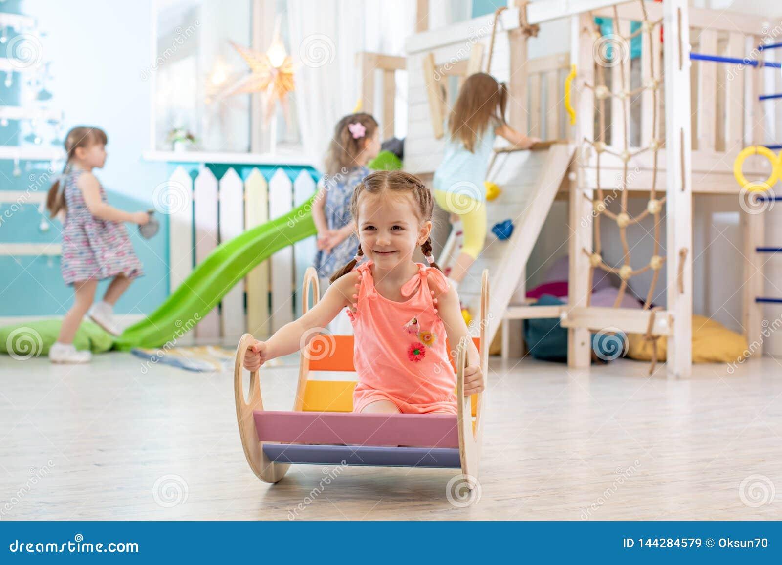 Szczęśliwa mała dziewczynka bawić się w playroom