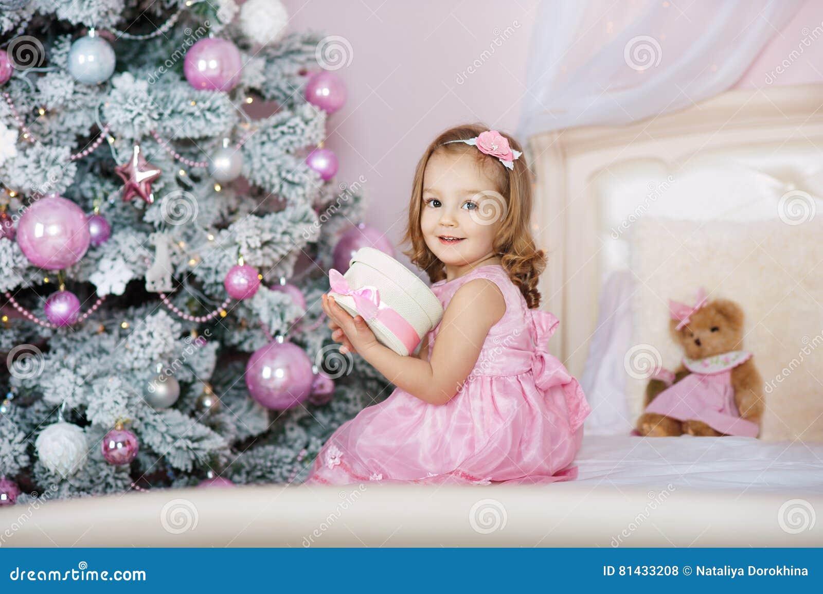 Szczęśliwa mała uśmiechnięta dziewczyna z boże narodzenie prezenta pudełkiem