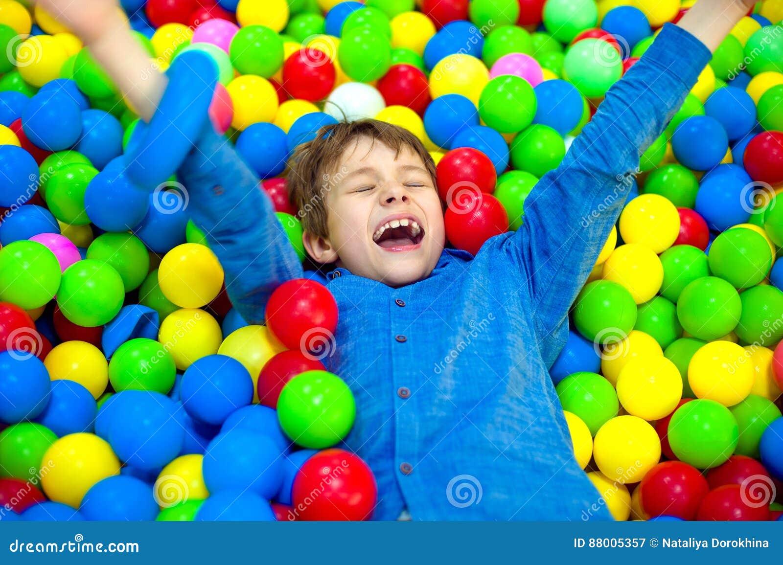Szczęśliwa małe dziecko chłopiec bawić się przy kolorowego plastikowego piłki boiska wysokim widokiem Śmieszny dziecko ma zabawę