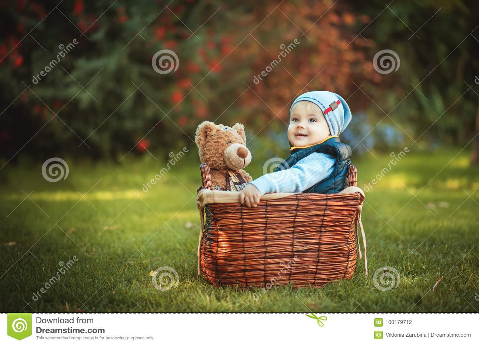 Szczęśliwa małe dziecko chłopiec bawić się z niedźwiedź zabawką podczas gdy siedzący w koszu na zielonym jesień gazonie Dzieci ci