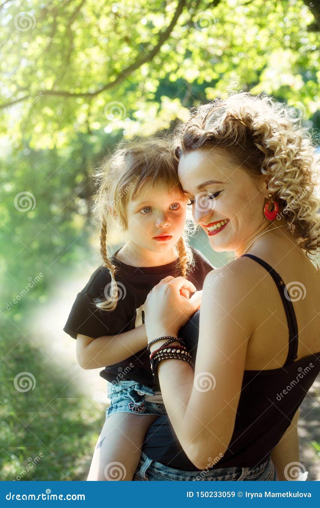 Szczęśliwa matka ściska wpólnie z córki jednakowym spojrzeniem