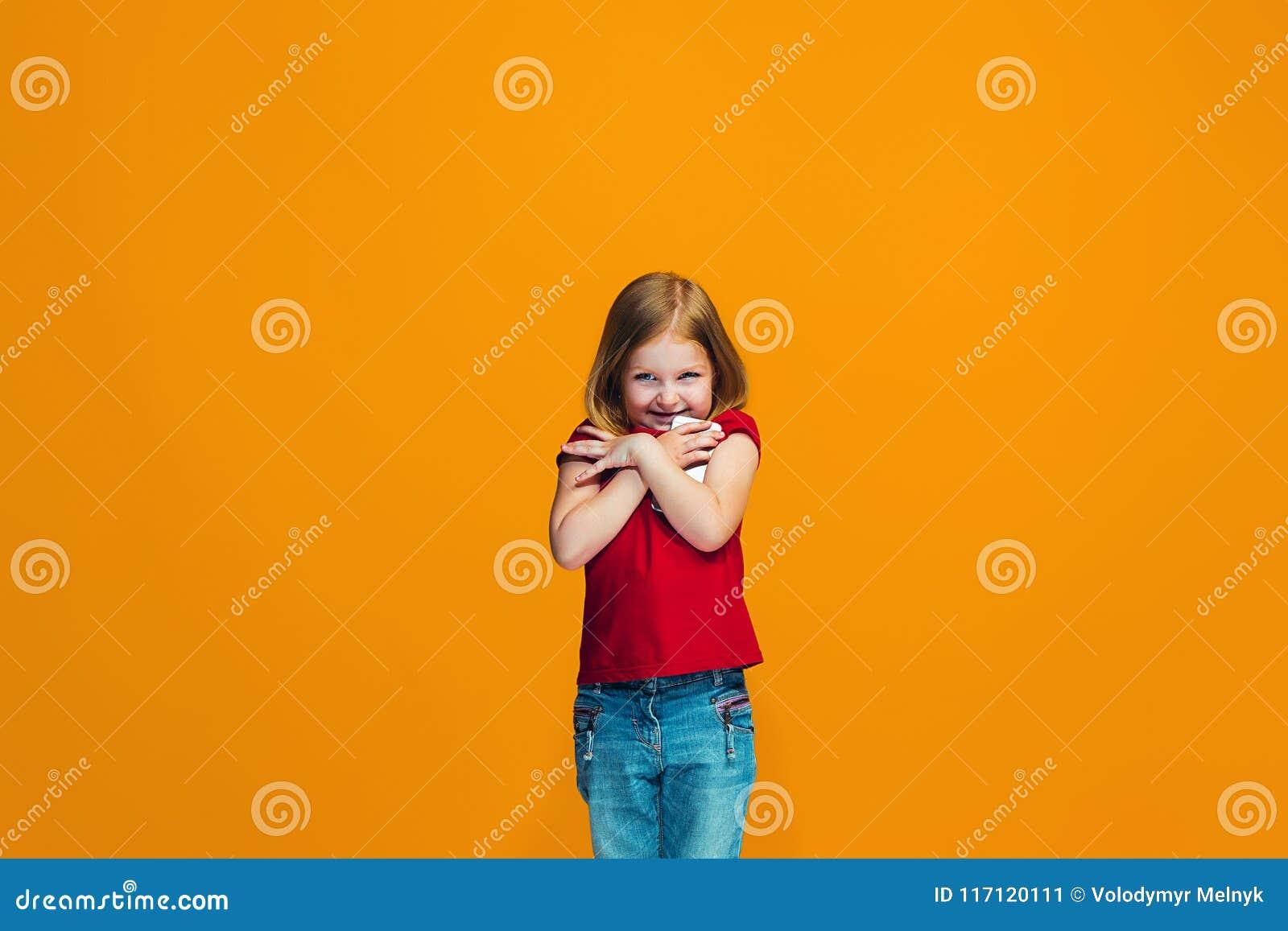 Szczęśliwa nastoletnia dziewczyny pozycja i ono uśmiecha się przeciw pomarańczowemu tłu
