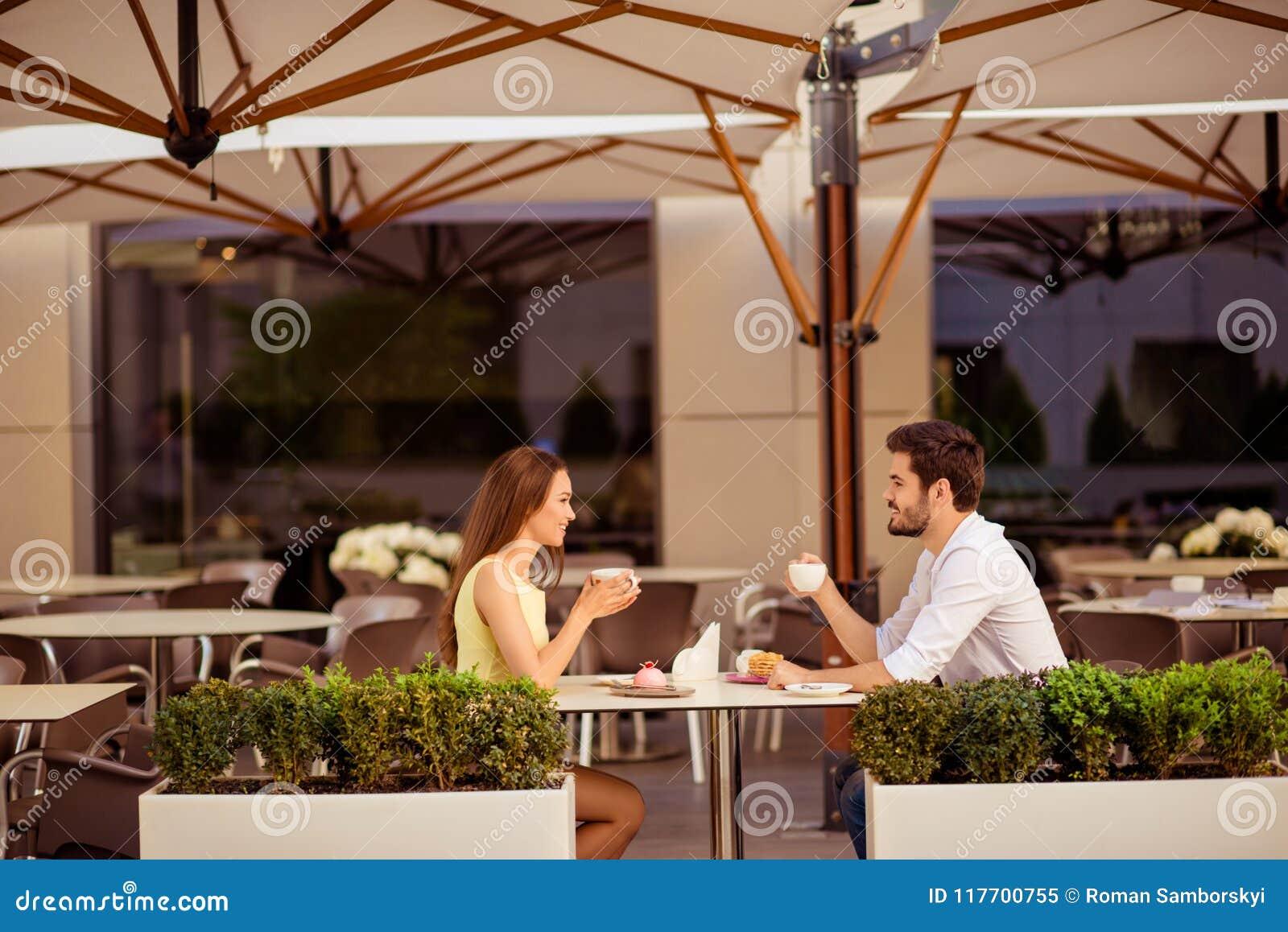 Szczęśliwa para małżeńska jest na miodowej księżyc, mieć śniadanio-lunch w ładnej kawiarni z nowożytnym wnętrzem, lekki lato tara