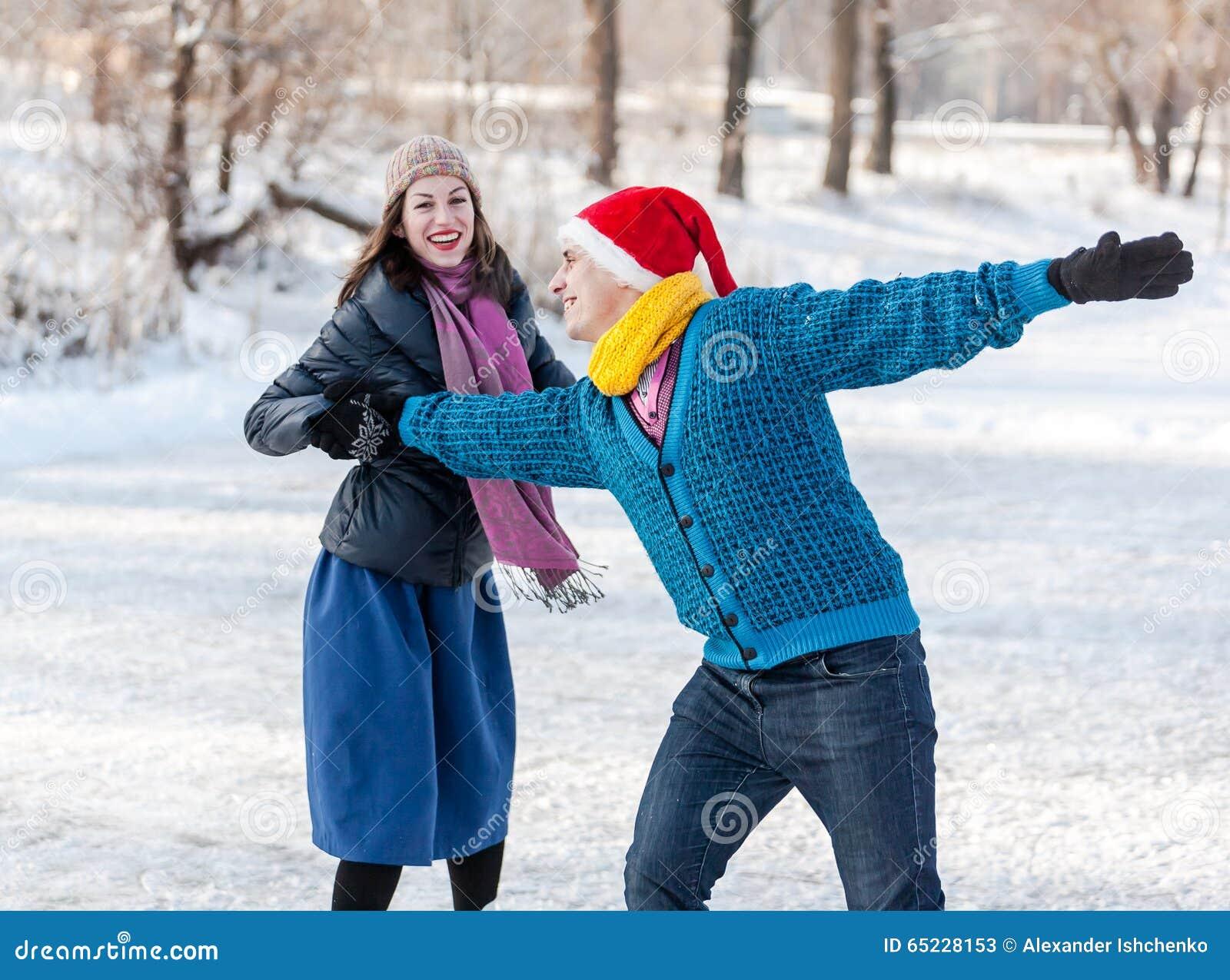 Szczęśliwa para ma zabawy jazda na łyżwach na lodowisku outdoors