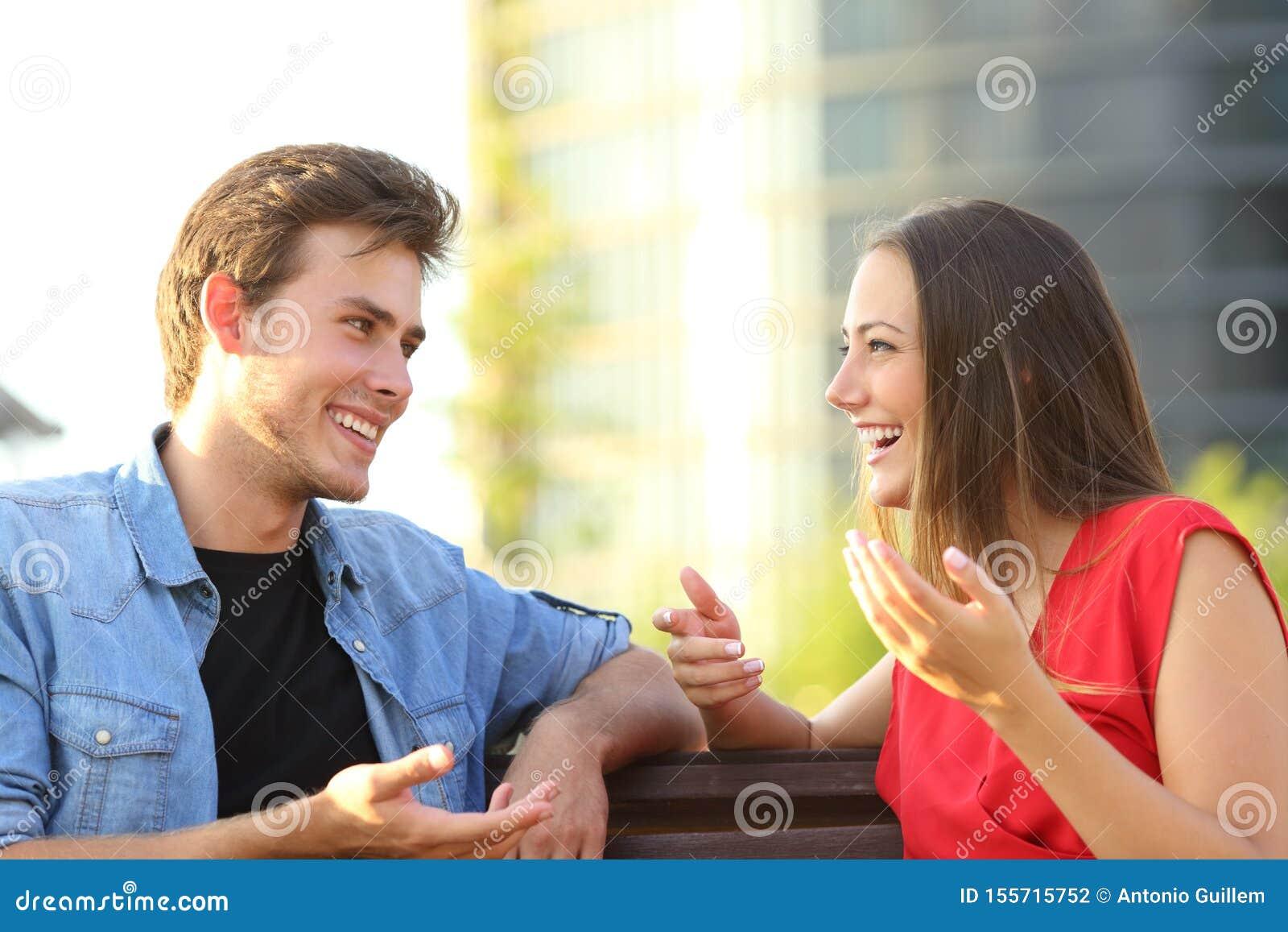 Szczęśliwa para opowiada siedzieć na ławce w ulicie