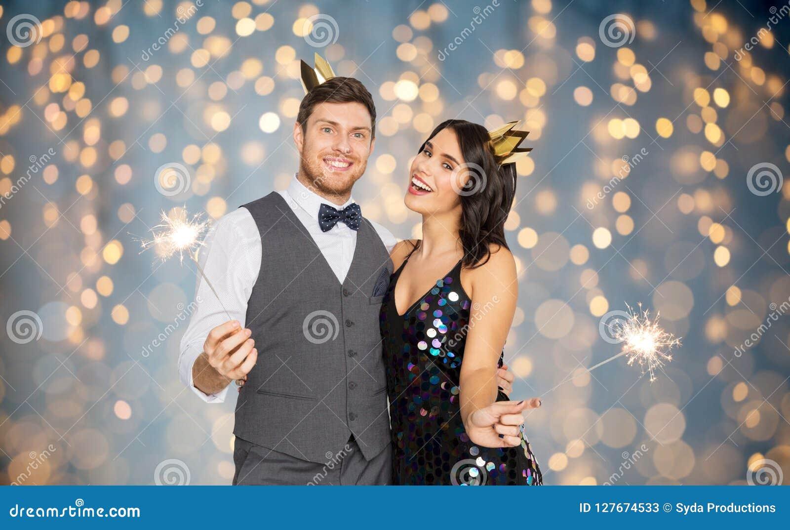 Szczęśliwa para z koronami i sparklers przy przyjęciem
