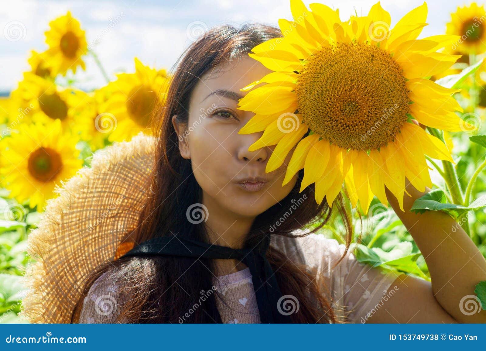 Szczęśliwa piękna azjatykcia kobieta z słomianym kapeluszem w słonecznika polu