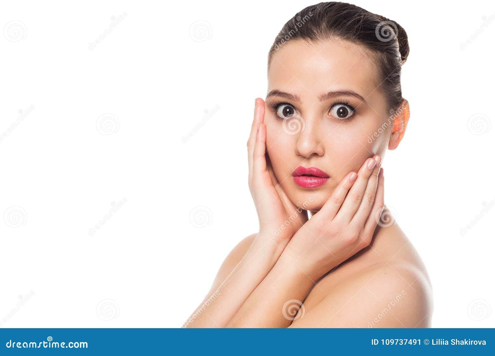 Szczęśliwa piękna dziewczyna trzyma jej policzki z śmiechem patrzeje strona Ekspresyjni wyrazy twarzy Kosmetologia i zdrój
