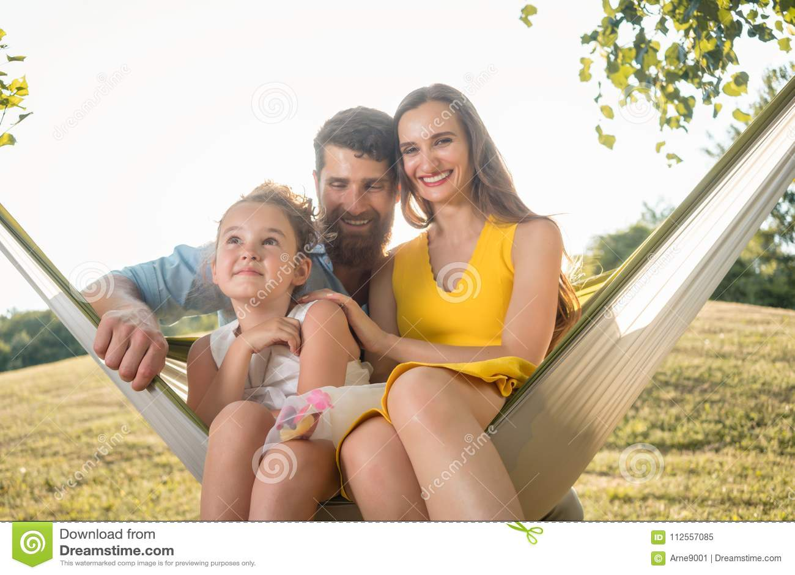 Szczęśliwa piękna kobieta i przystojny mąż pozuje wraz z ich córką