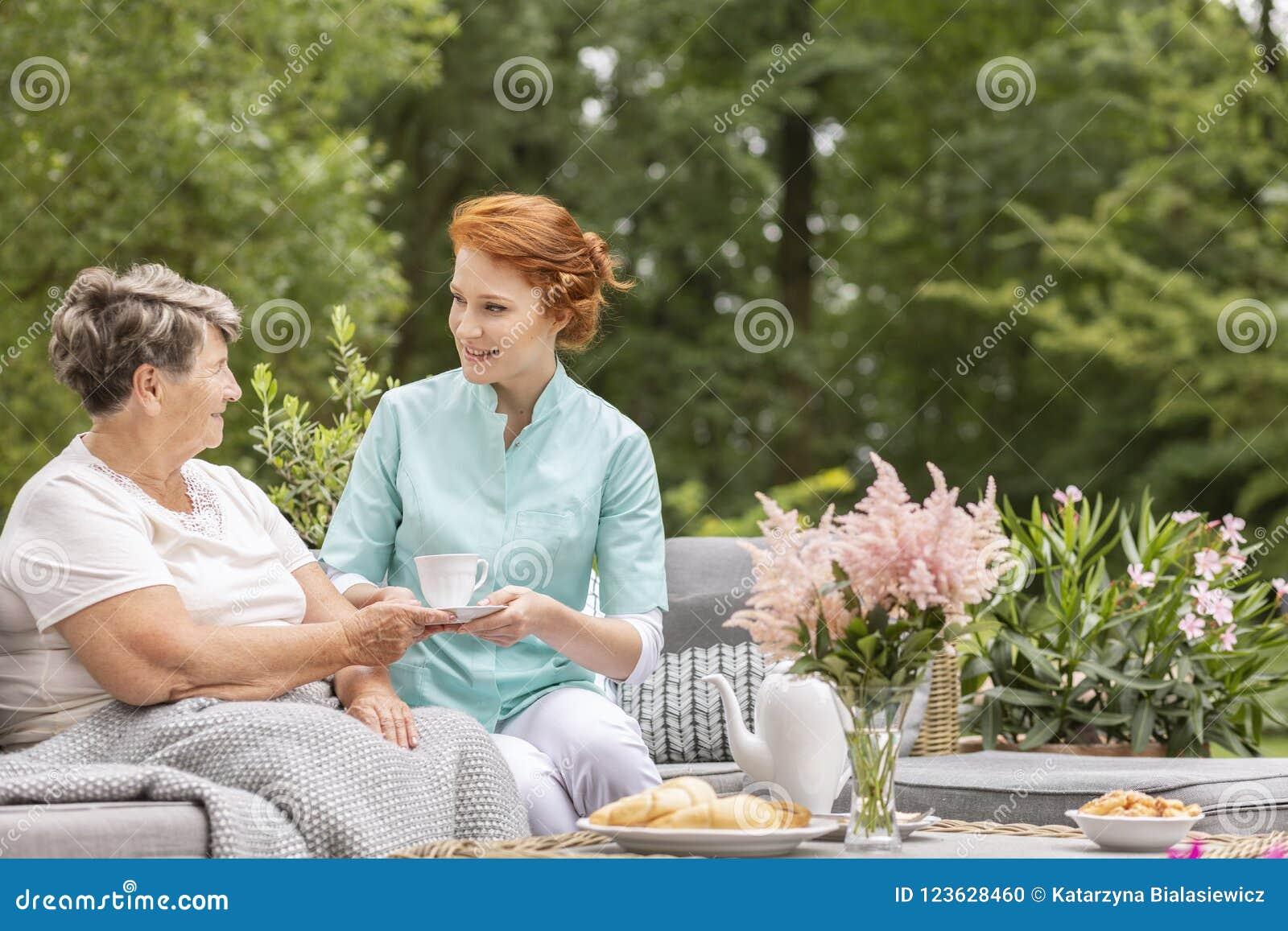 Szczęśliwa pielęgniarka daje herbaty starsza kobieta podczas gdy jedzący śniadanie o