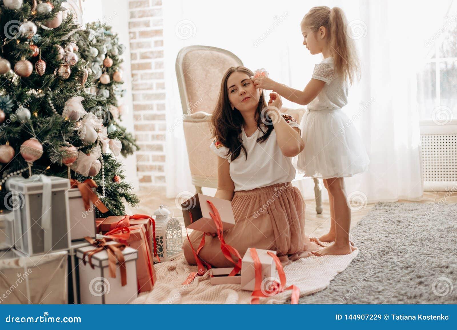 Szczęśliwa potomstwo matka i jej mała córka w ładnej sukni siedzimy ne