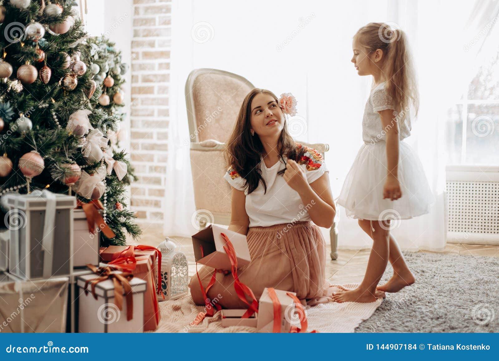 Szczęśliwa potomstwo matka z kwiatem w jej włosy i jej mała córka w ładnej sukni siedzimy blisko nowego roku drzewa i otwie