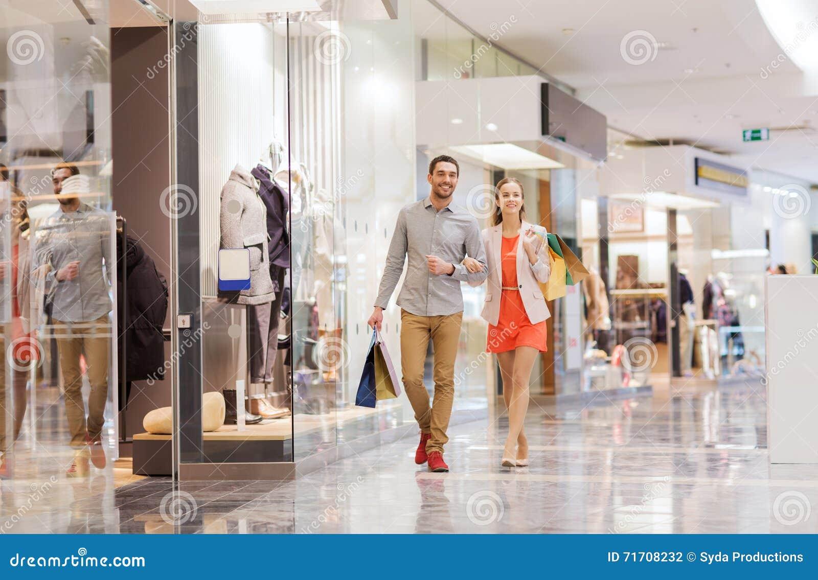 Szczęśliwa potomstwo para z torba na zakupy w centrum handlowym