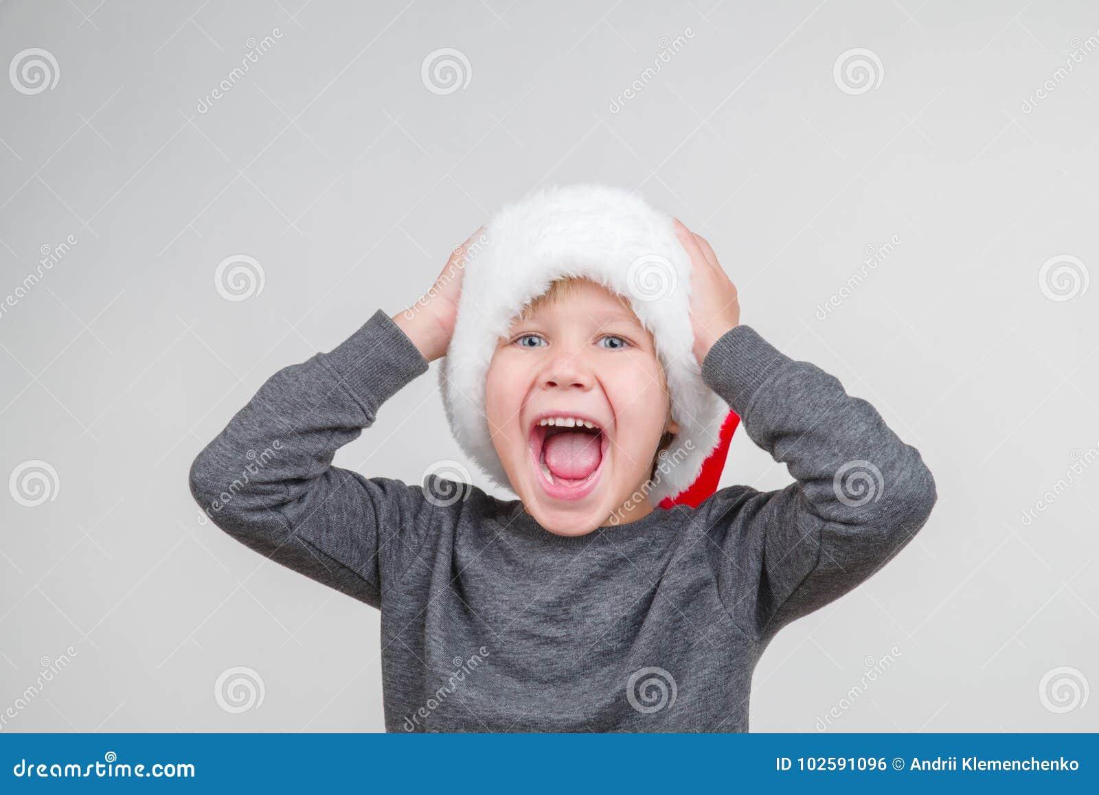 Szczęśliwa przystojna chłopiec pozuje w studiu Wakacyjny pojęcie