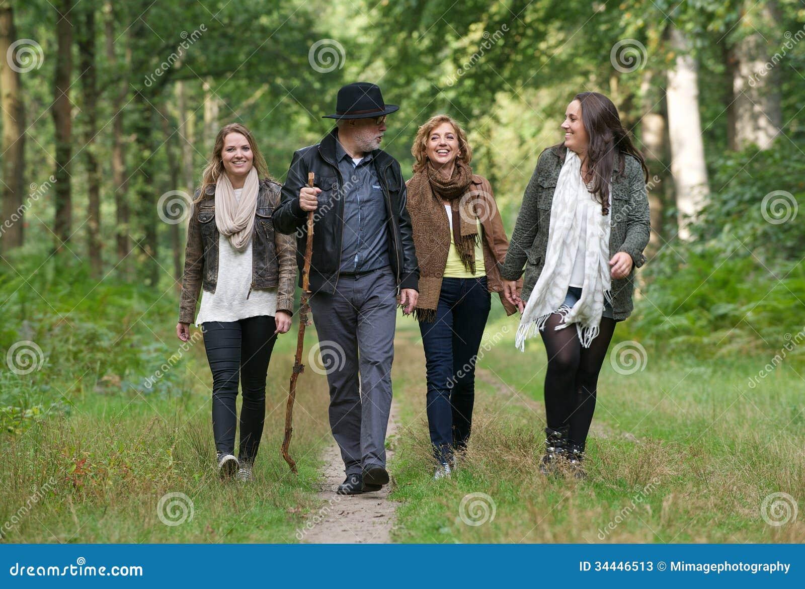 Szczęśliwa rodzina cieszy się przespacerowanie przez drewien