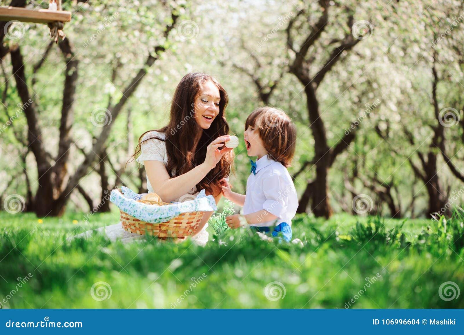 Szczęśliwa rodzina na pinkinie dla matka dnia Mamy i berbecia syna łasowania cukierki plenerowi w wiośnie