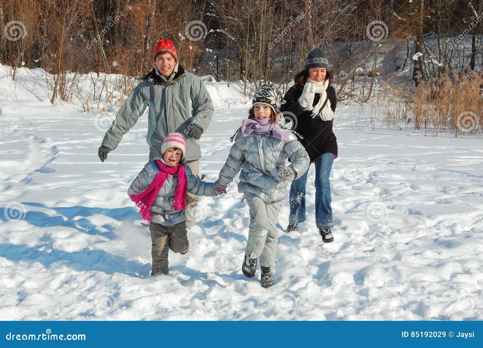 Szczęśliwa rodzina w zimie, mieć zabawę z śniegiem outdoors