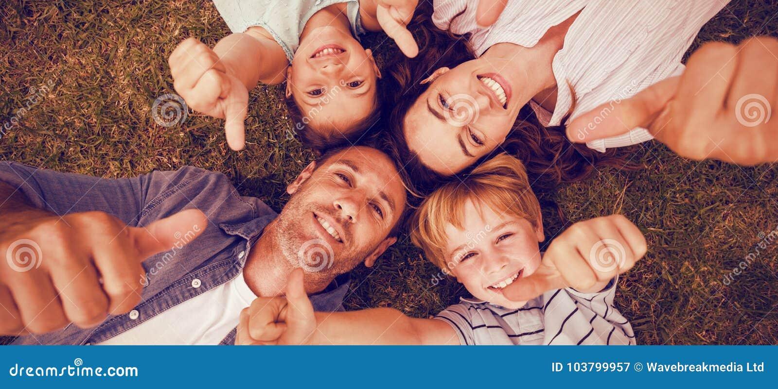 Szczęśliwa rodzina wpólnie gestykuluje aprobaty w parku