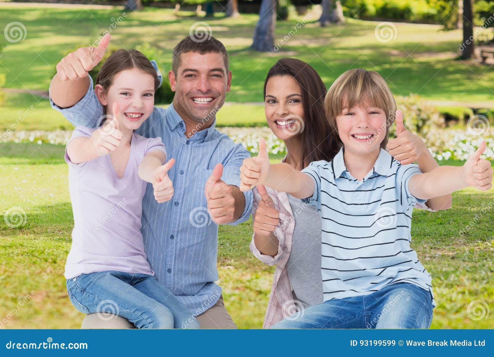Szczęśliwa rodzina z aprobatami na ogródzie