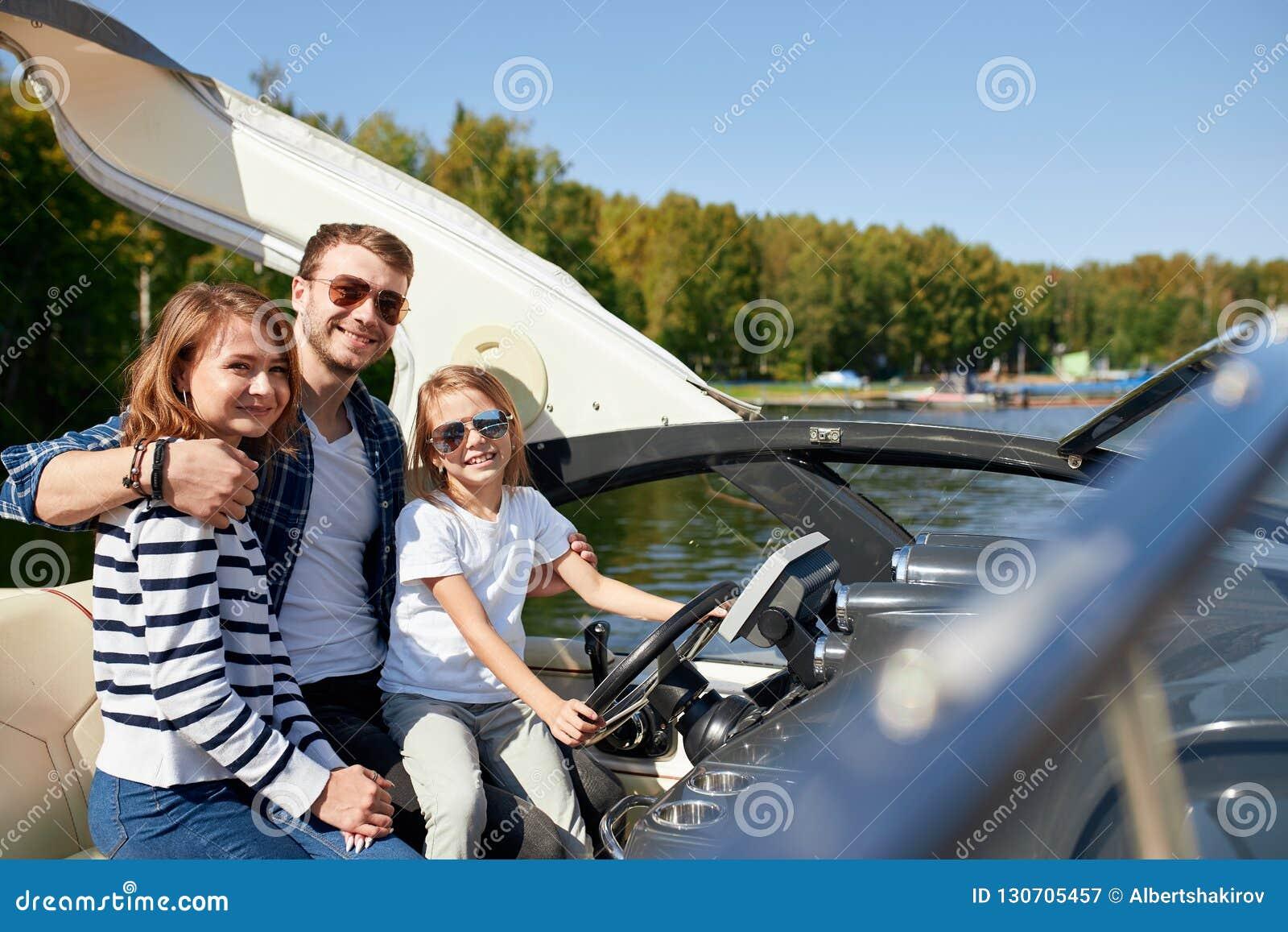 Szczęśliwa rodzina z córką na żeglowanie łodzi przy pogodnym jesień dniem