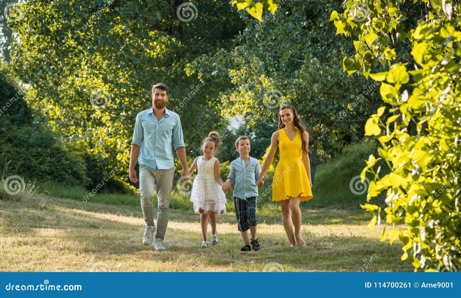 Szczęśliwa rodzina z dwa dziećmi trzyma ręki podczas rekreacyjnego spaceru w parku