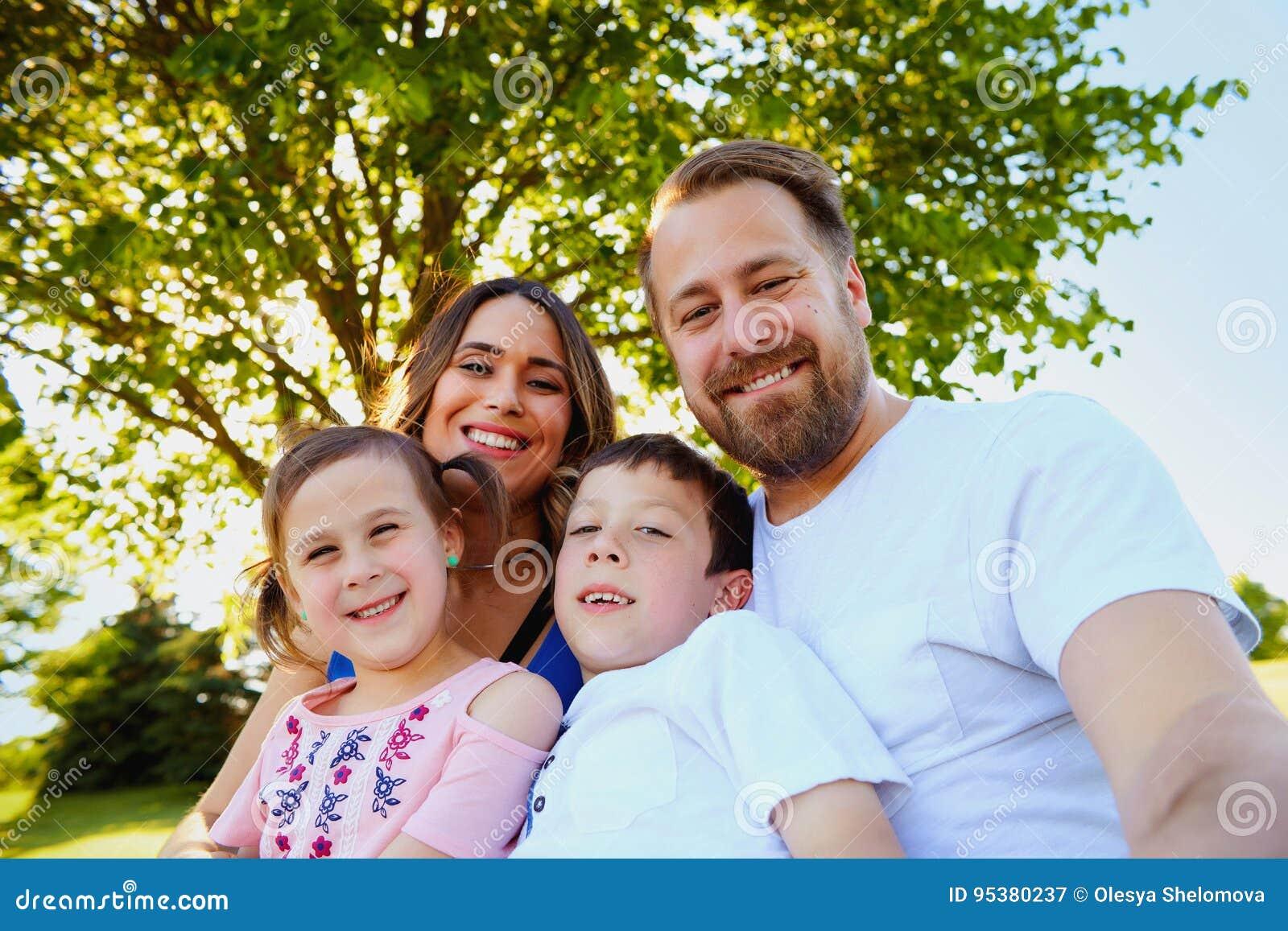 Szczęśliwa rodzina z dziećmi bierze selfie w parku