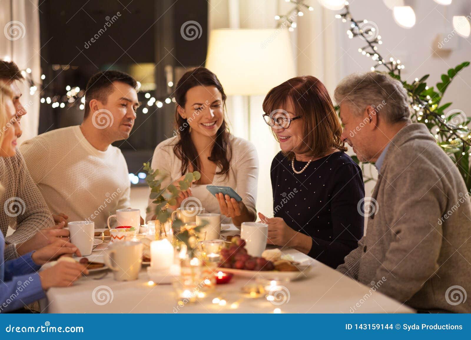 Szczęśliwa rodzina z smartphone przy herbacianym przyjęciem w domu