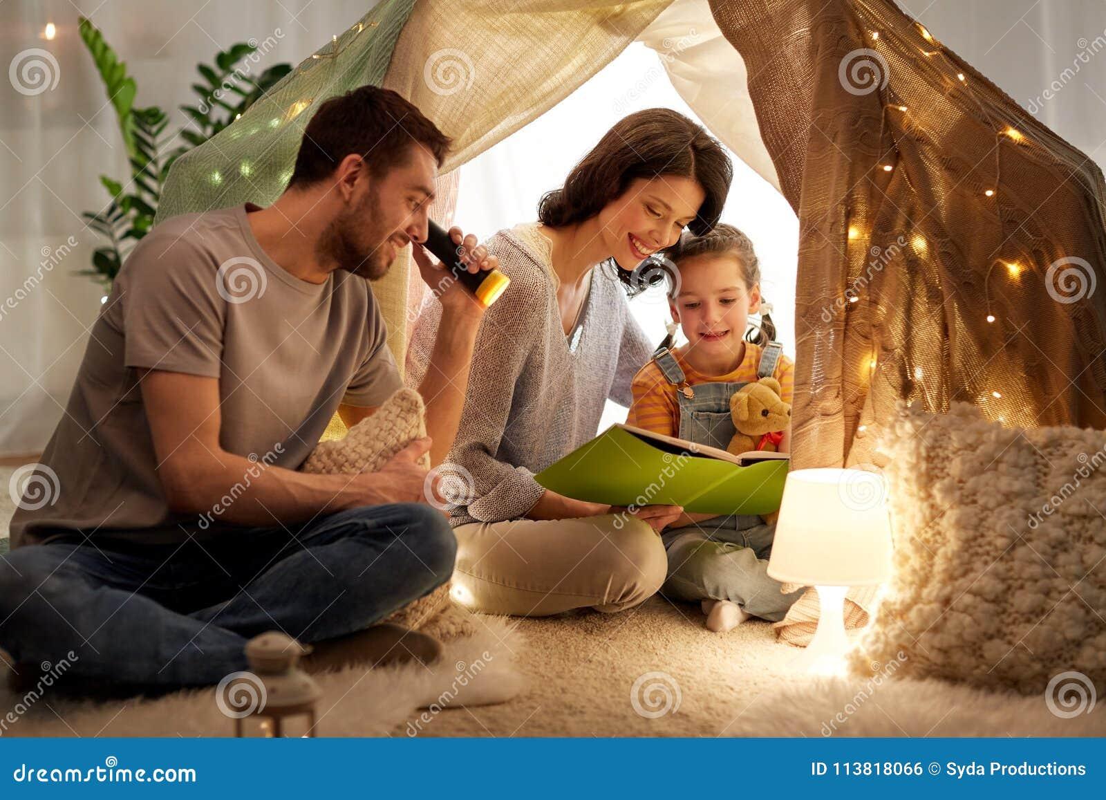 Szczęśliwa rodzinna czytelnicza książka w dzieciaka namiocie w domu