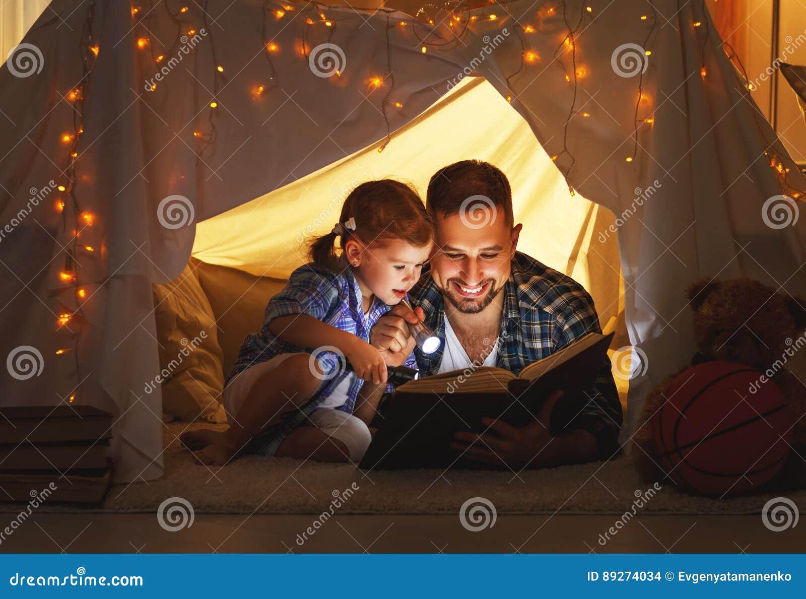 Szczęśliwa rodzinna ojca i dziecka córka czyta książkę w namiocie