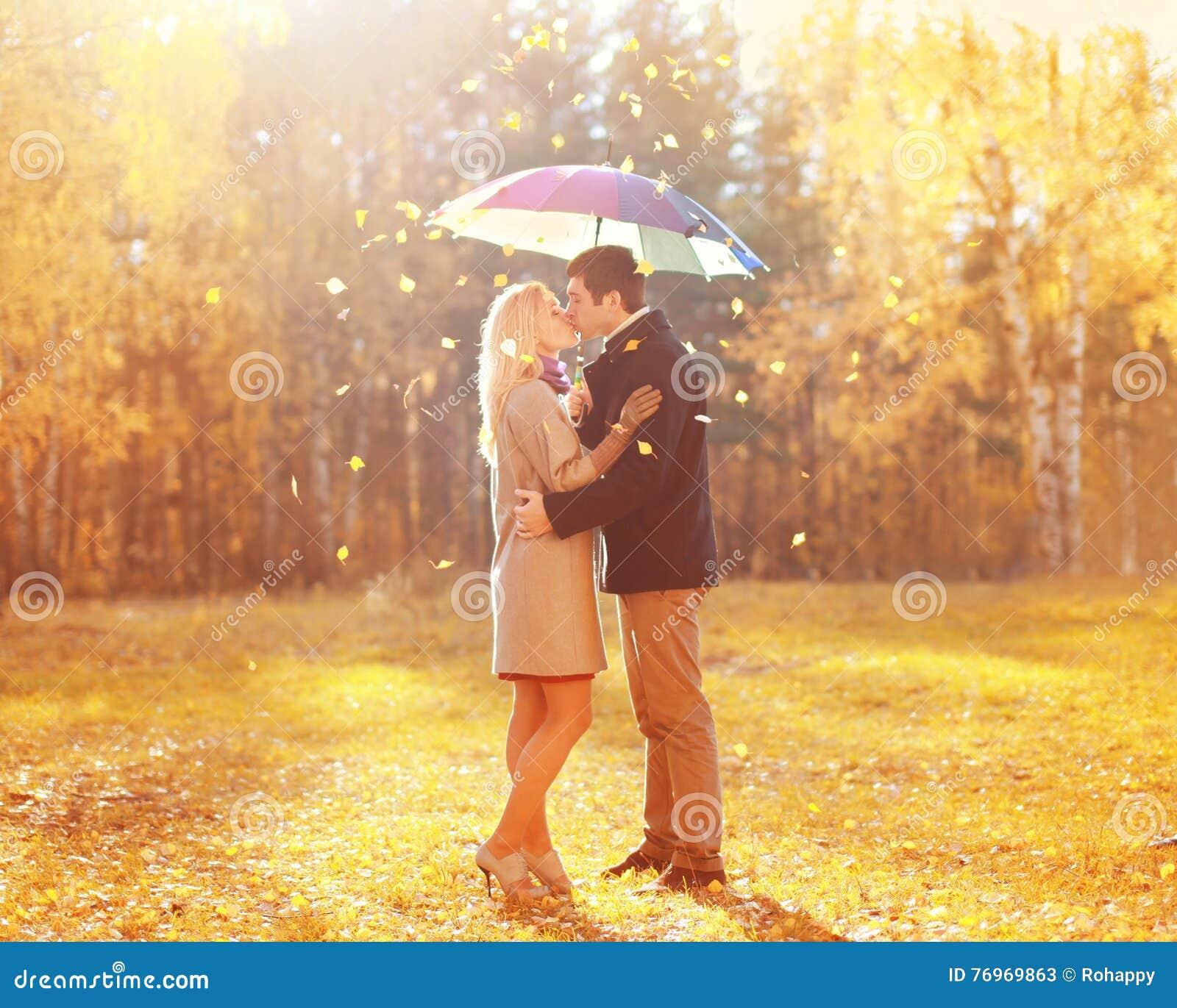 Szczęśliwa romantyczna całowanie para w miłości z kolorowym parasolem przy ciepłym słonecznym dniem nad żółtymi latającymi liśćmi