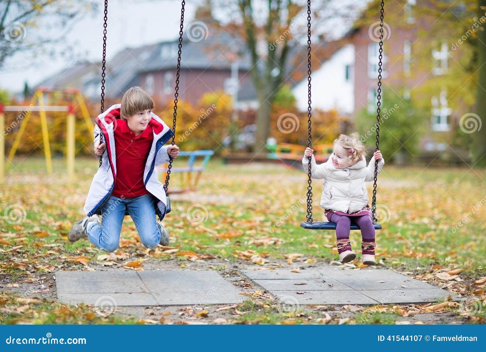 Szczęśliwa roześmiana chłopiec i dziecka siostra bawić się na huśtawce