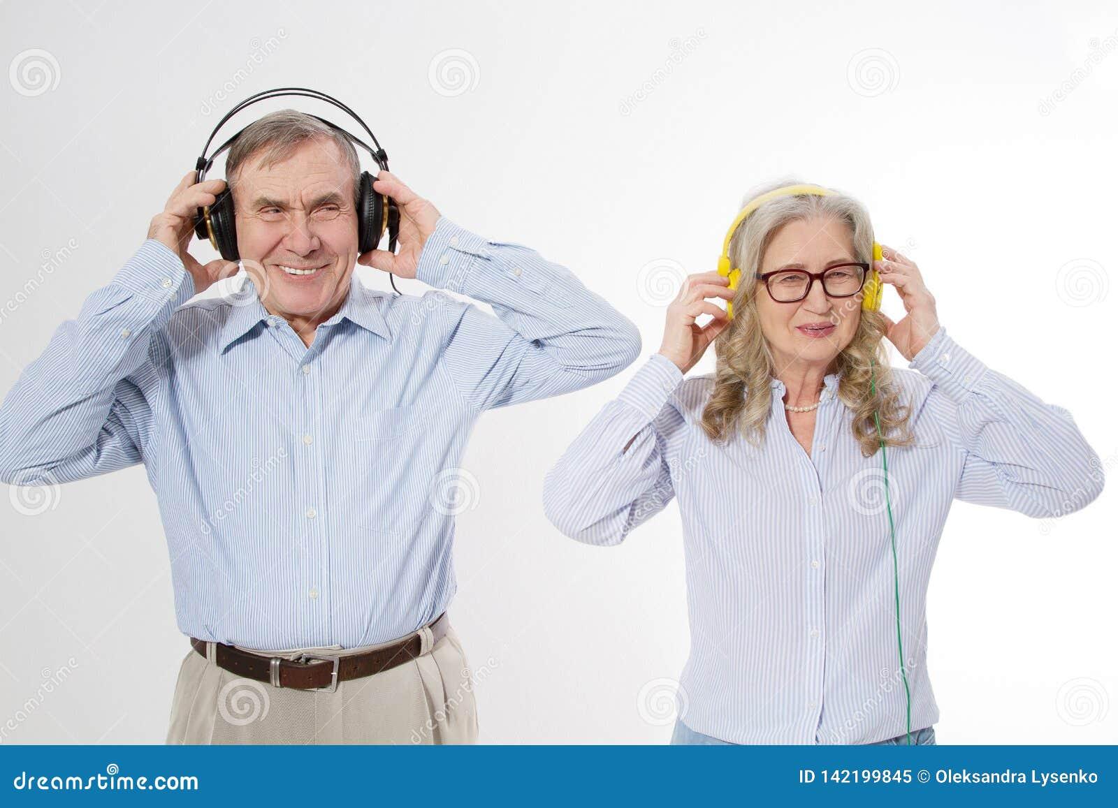 Szczęśliwa senior para lesten muzyka w hełmofonach odizolowywających na białym tle Starsza rodzinna zabawy dyskoteka i pisitive z