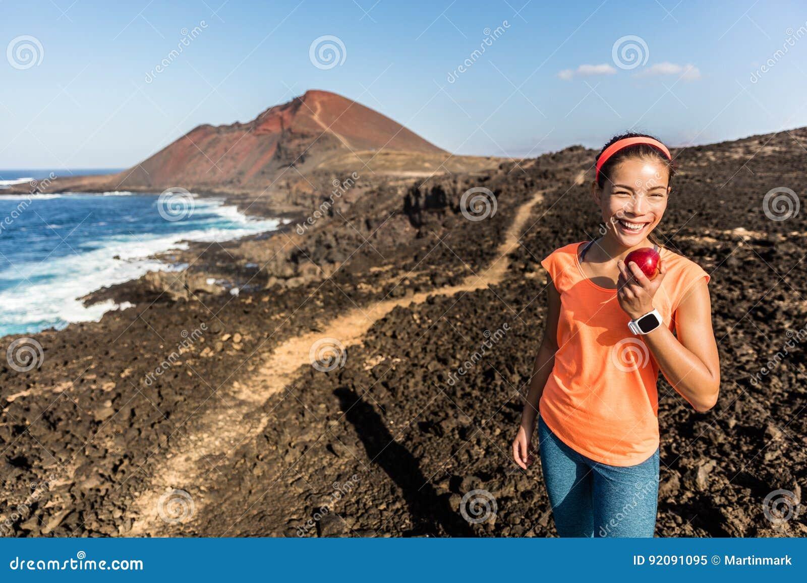 Szczęśliwa sprawności fizycznej kobieta na wycieczkować śladu łasowania jabłka