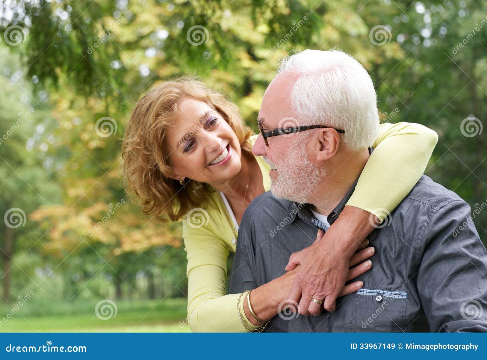 Szczęśliwa stara para uśmiechnięta i patrzeje each inny outdoors