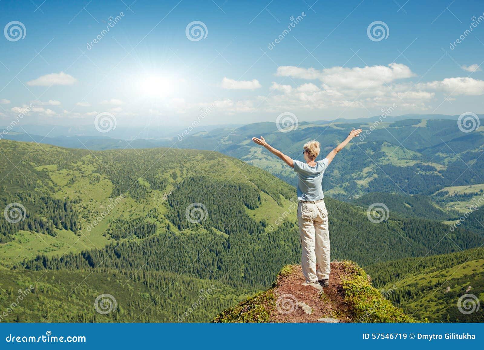 Szczęśliwa starsza kobieta cieszy się naturę w górach