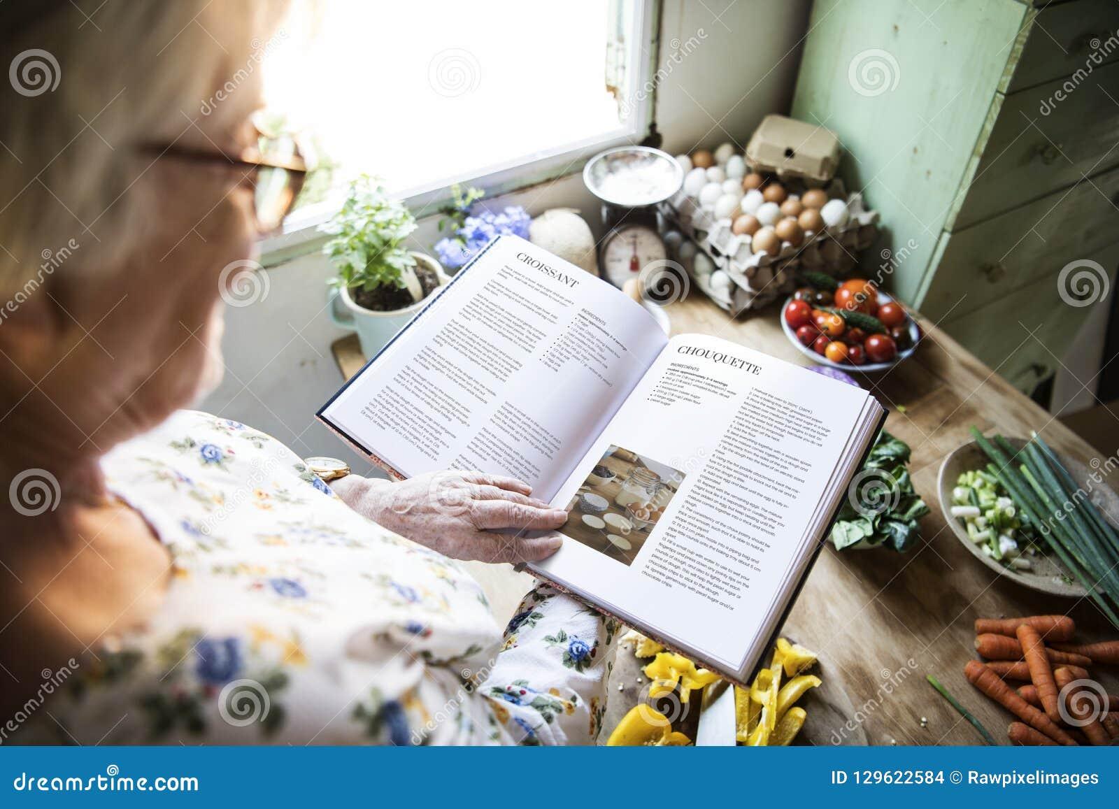 Szczęśliwa starsza kobieta czyta książkę kucharska