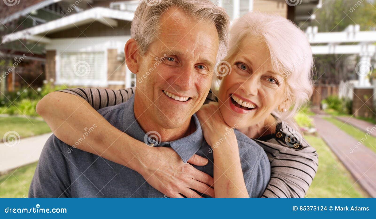 Szczęśliwa starsza para roześmiana i ono uśmiecha się przed ich domem