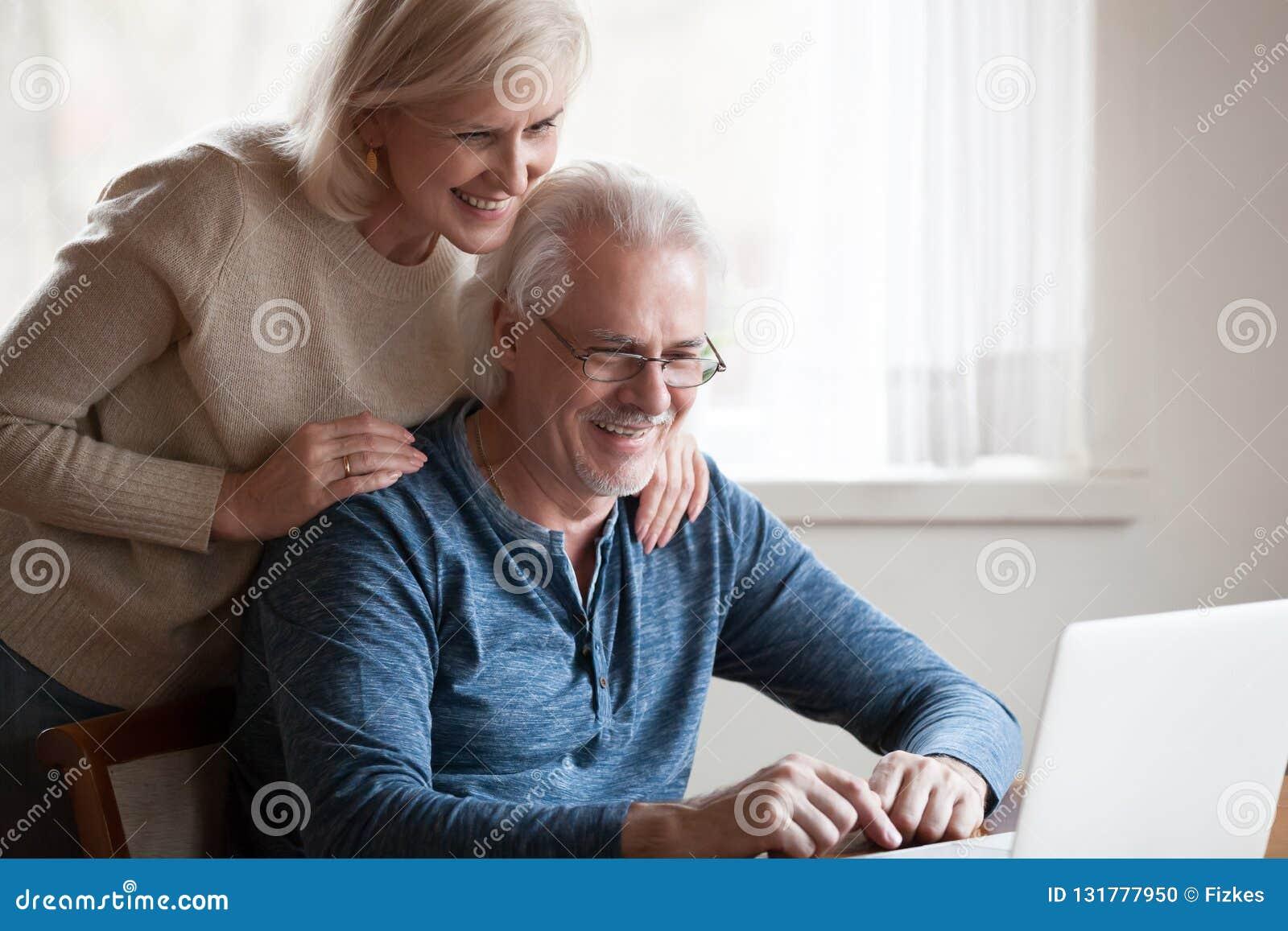 Szczęśliwa starzejąca się para patrzeje laptopu ekranu ono uśmiecha się