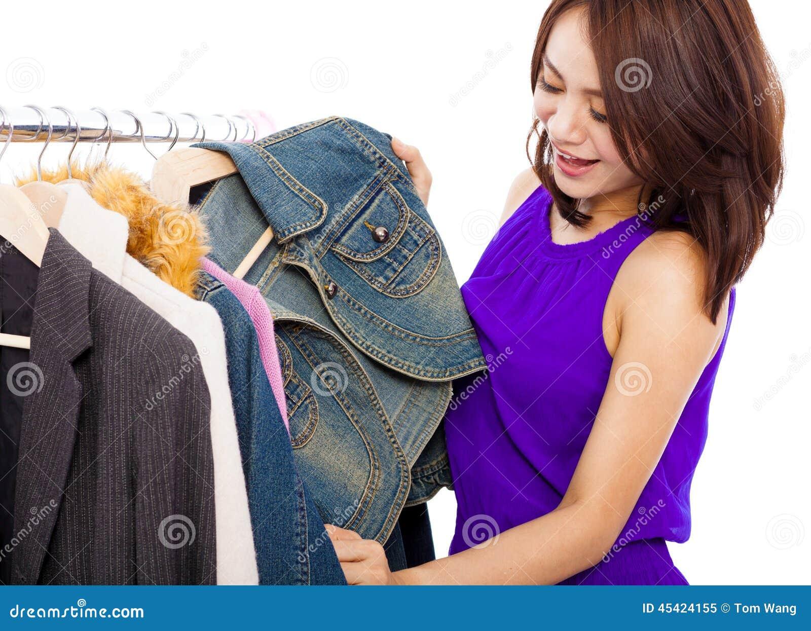 Szczęśliwa uśmiechnięta azjatykcia kobieta wybiera zakupy odziewa