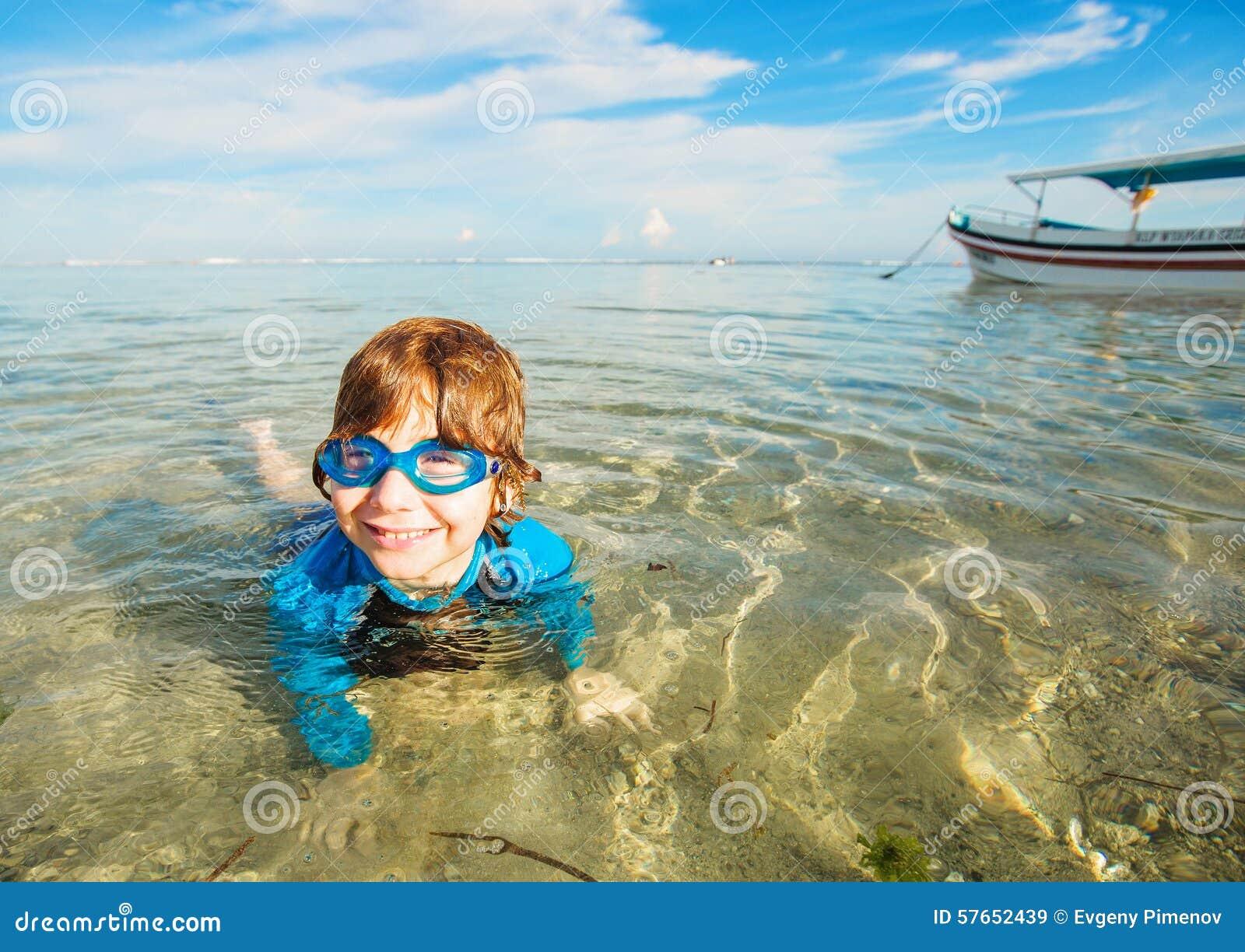 Szczęśliwa uśmiechnięta chłopiec z gogle na pływaniu w płyciznie