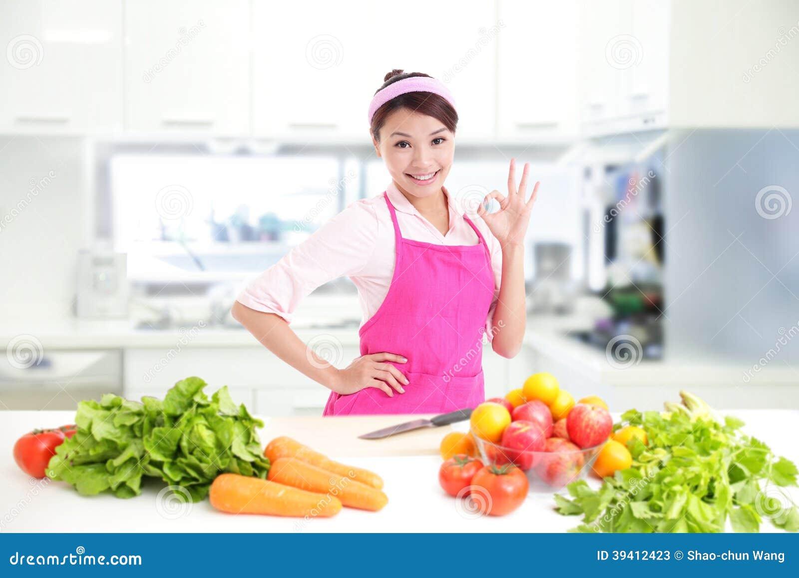 Szczęśliwa uśmiechnięta kobieta w kuchni