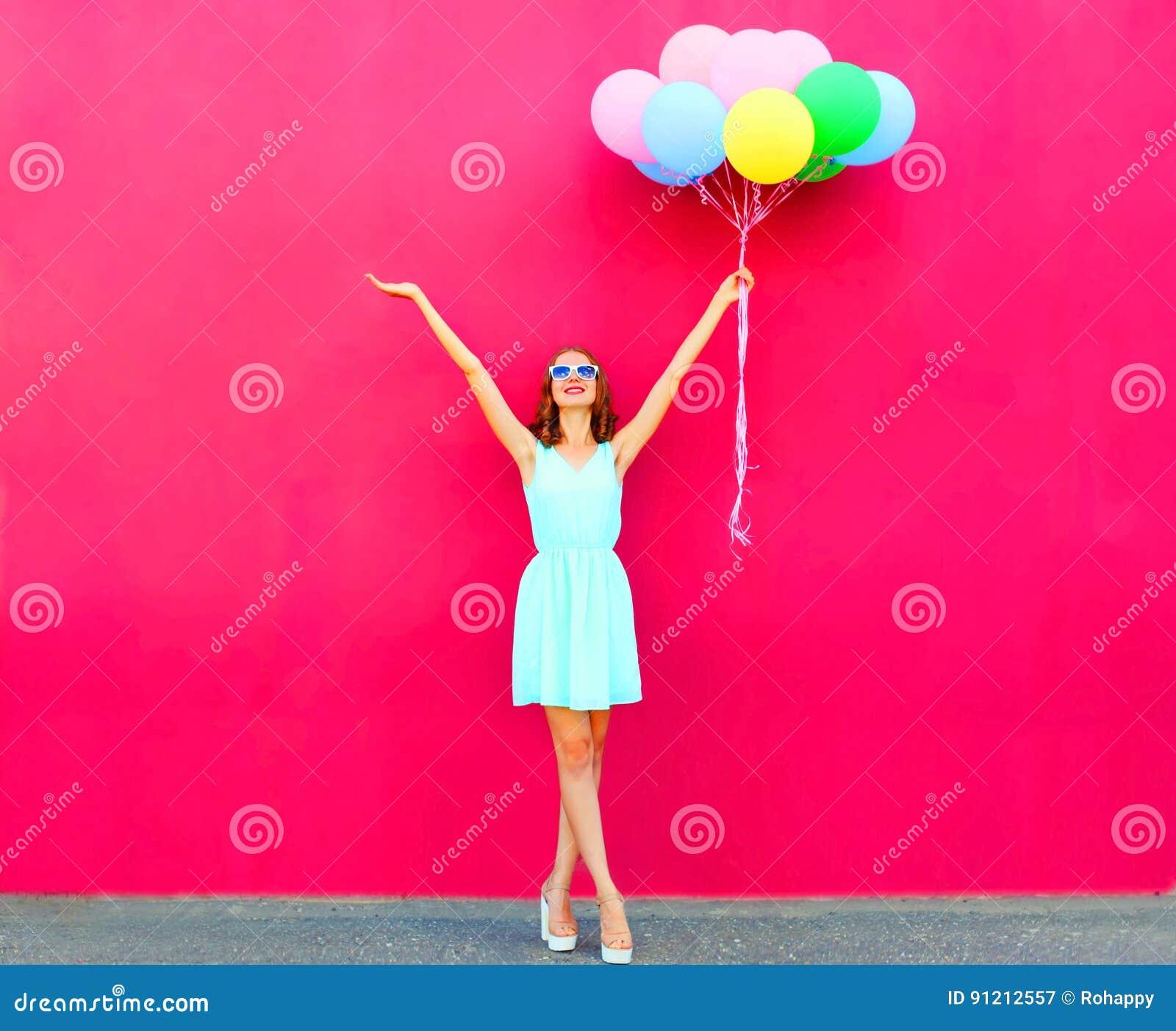 Szczęśliwa uśmiechnięta kobieta z lotniczy kolorowi balony nad różowym tłem