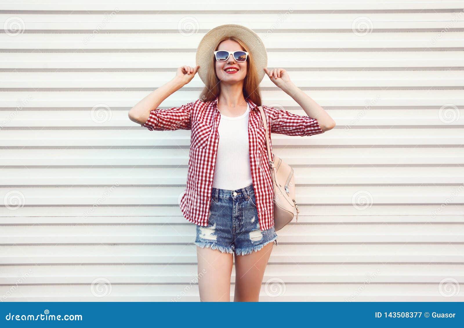 Szczęśliwa uśmiechnięta młoda kobieta pozuje w lata round słomianym kapeluszu, w kratkę koszula, zwiera na biel ścianie