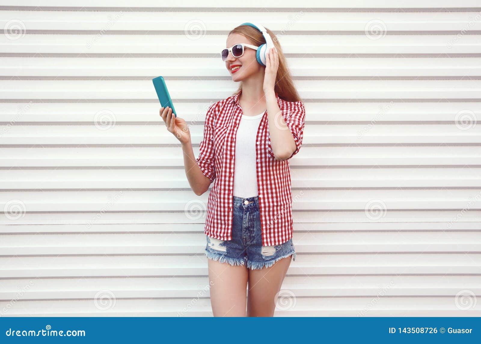 Szczęśliwa uśmiechnięta młoda kobieta słucha muzyka jest ubranym w kratkę koszula w hełmofonach z smartphone, skróty na bielu