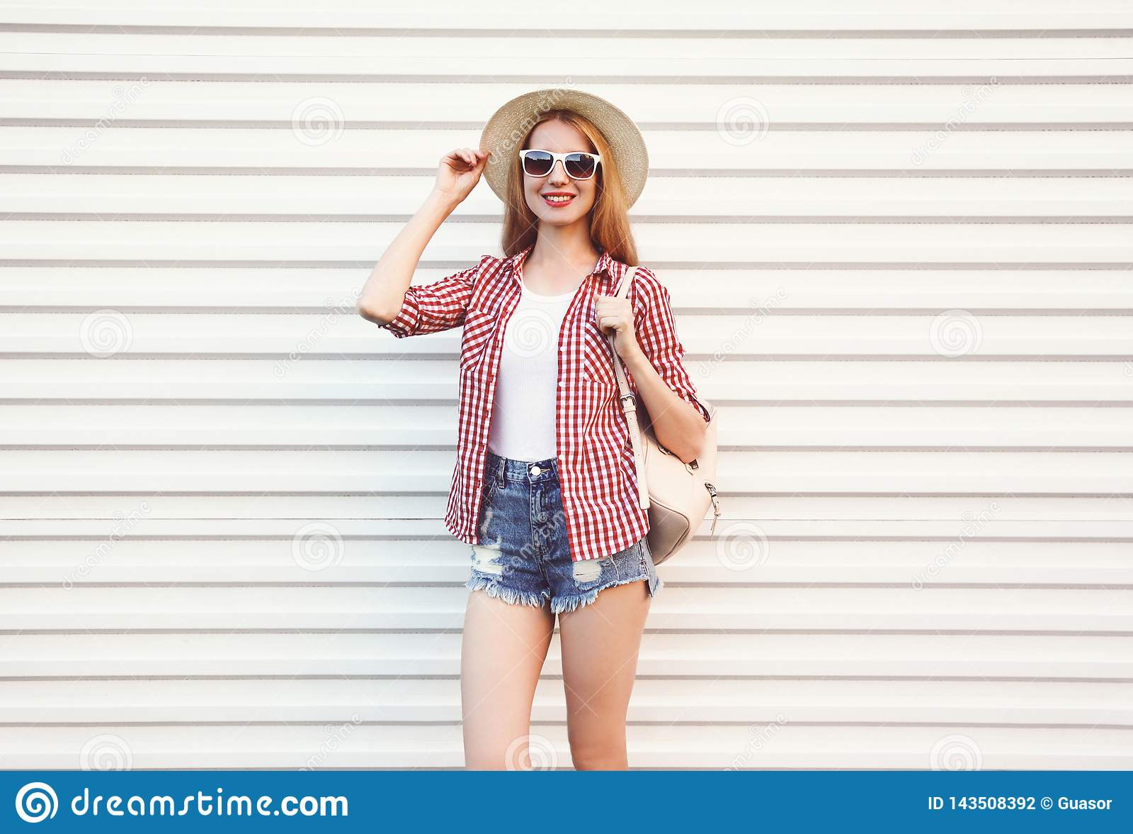 Szczęśliwa uśmiechnięta młoda kobieta w lata round słomianym kapeluszu, w kratkę koszula, zwiera pozować na biel ścianie