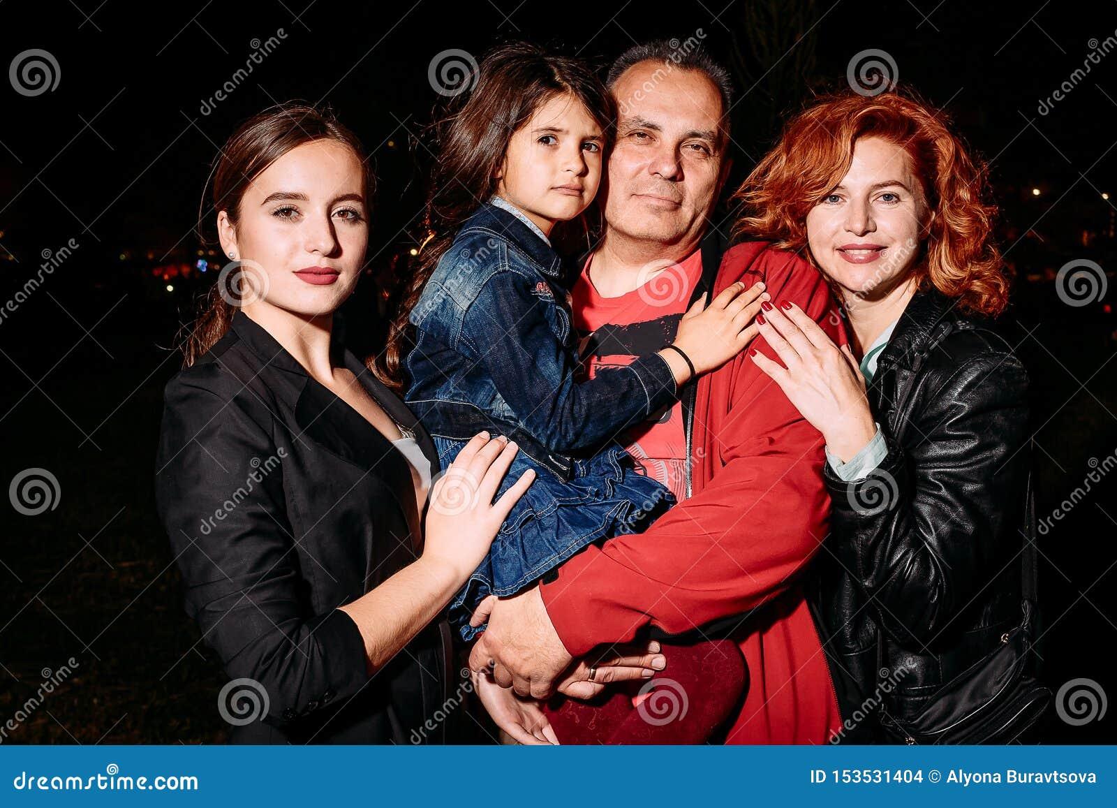 Szczęśliwa uśmiechnięta rodzina składająca się z czterech osób pozuje in camera przy nocą