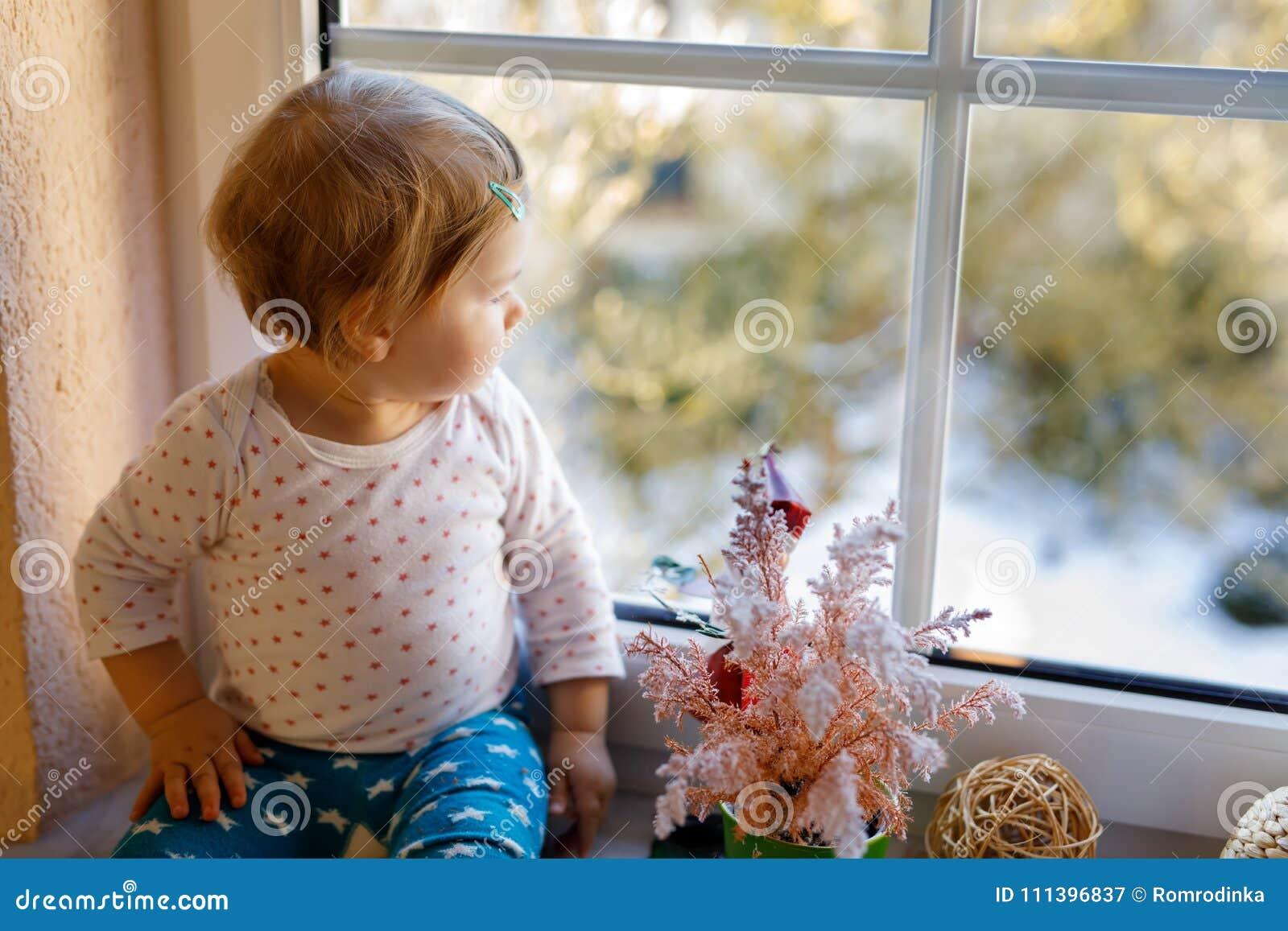 Szczęśliwa urocza śliczna dziewczynka siedzi blisko nadokiennego, przyglądającego outside na śniegu na dniu i
