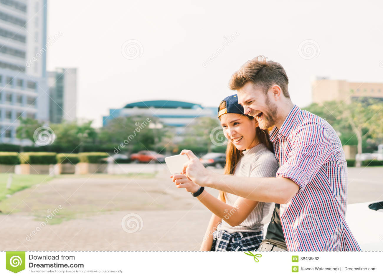 Szczęśliwa wieloetniczna para bierze selfie podczas zmierzchu w mieście, zabawie i technologii pojęciu, ono uśmiecha się, miłości