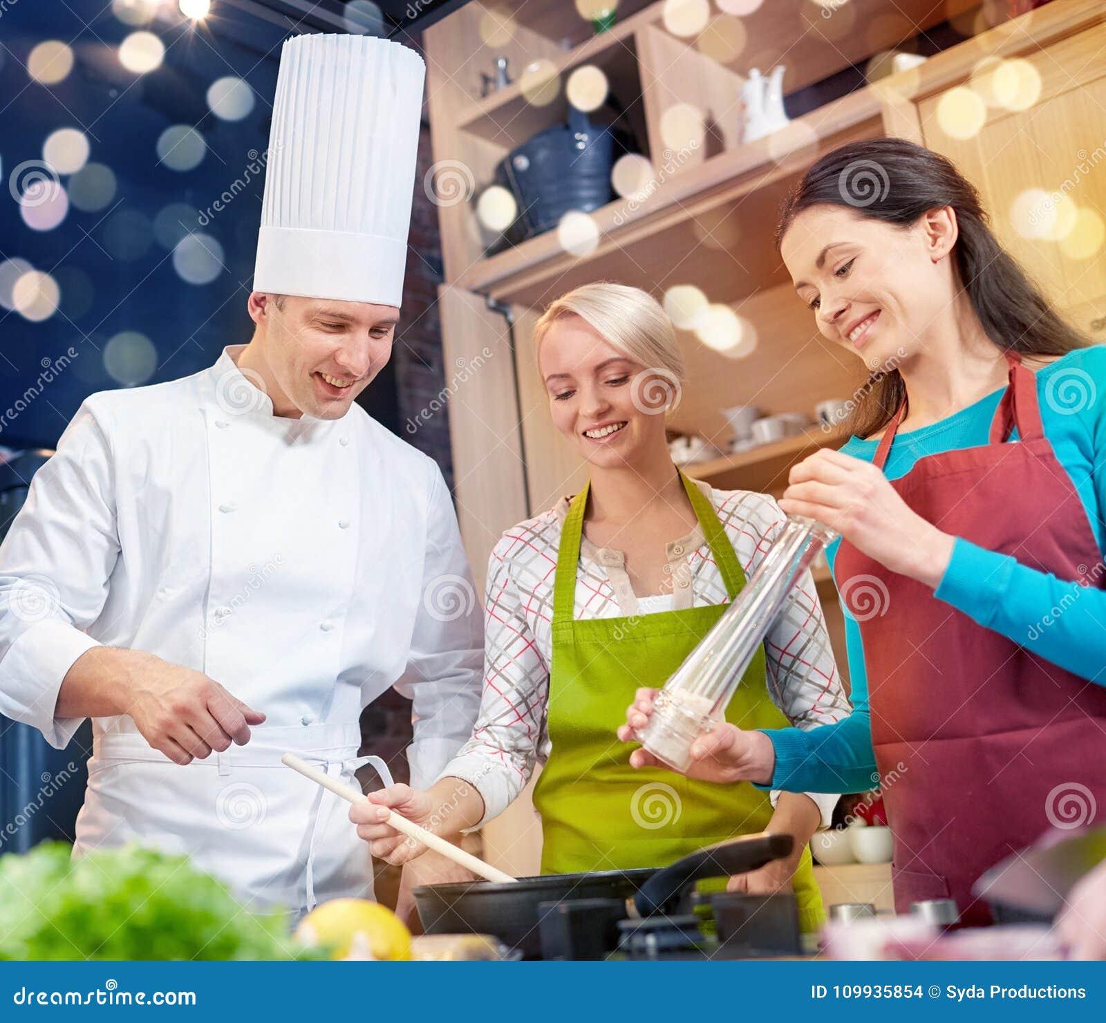 Szczęśliwe kobiety i szefa kuchni kucbarski kucharstwo w kuchni